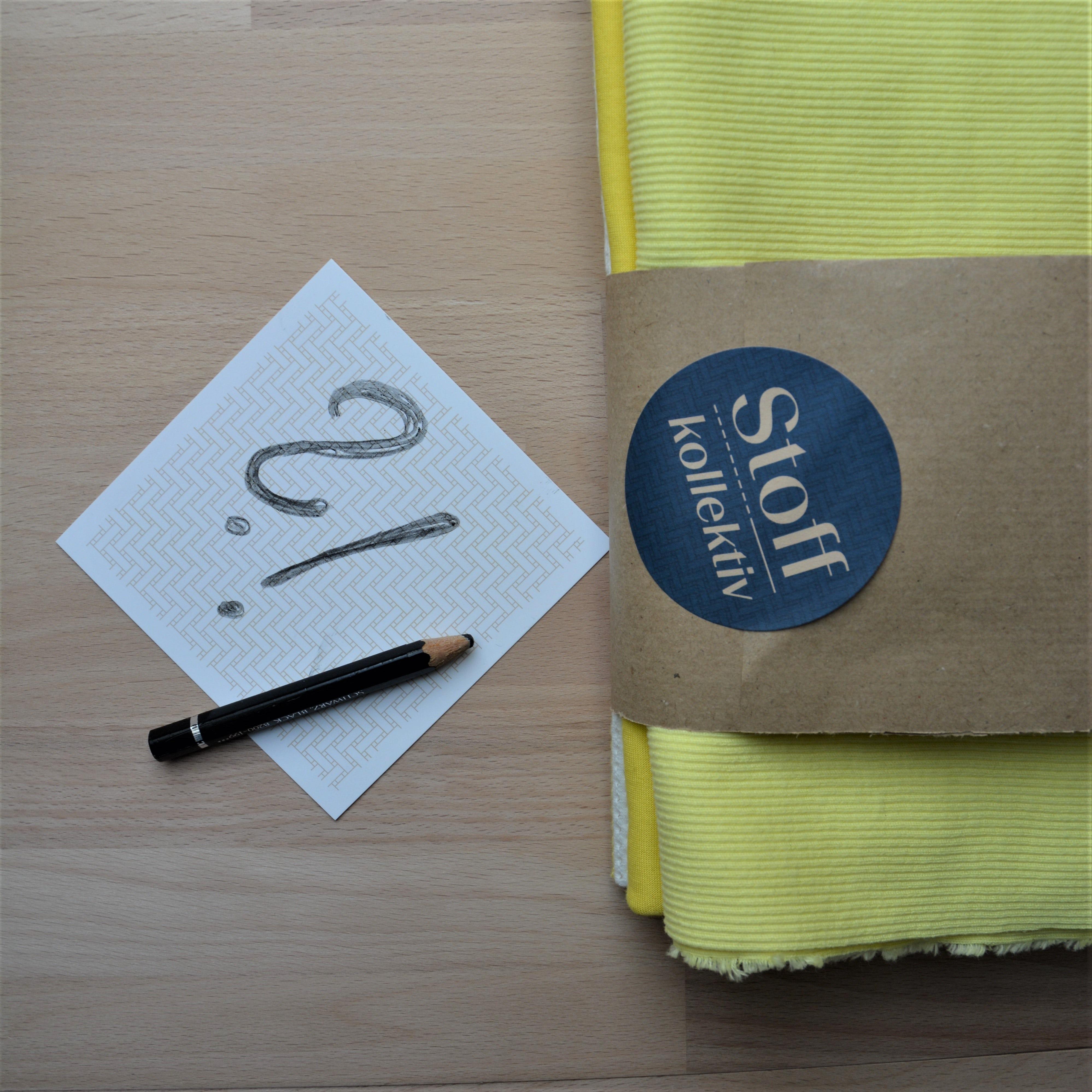 Stapel gelber Stoff eingepackt mit einem Streifen Packpapier mit Stoffkollektiv Sticker. Daneben ein Zettel mit Fragezeichen und Ausrufezeichen und Stift.