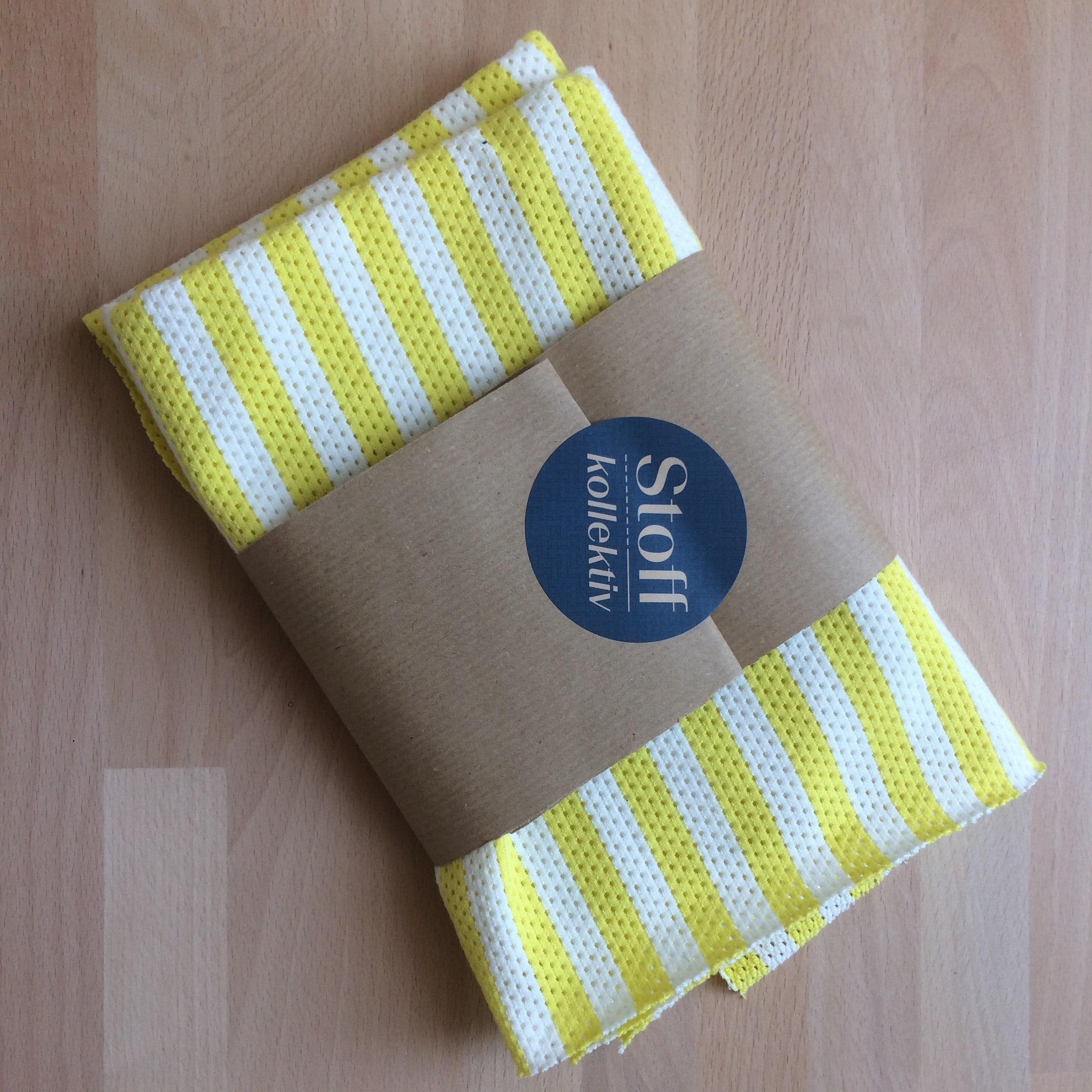 Gelb weiß gestreifter Stoff eingepackt in Streifen Packpapier und Stoffkollektiv Sticker.