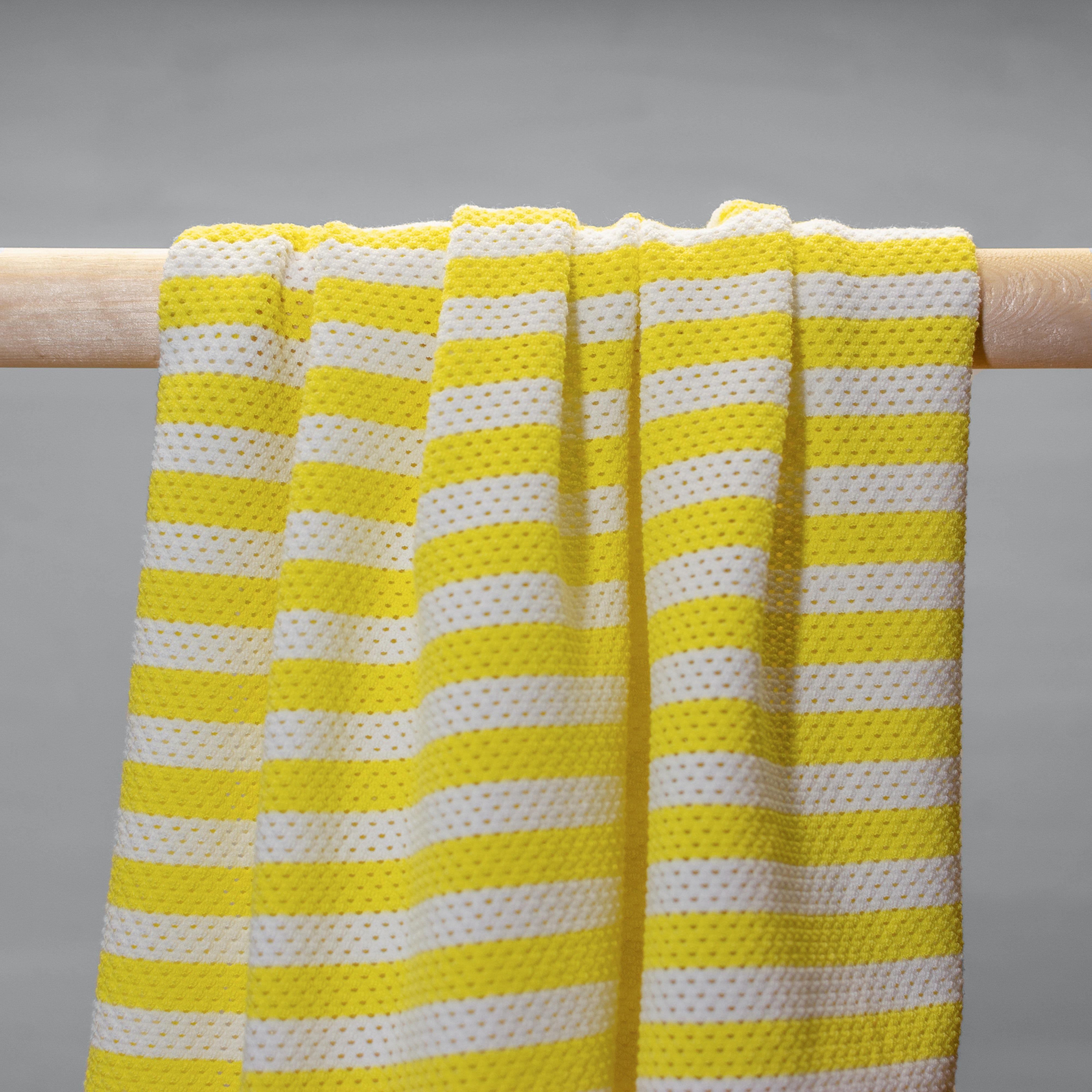 Mesh Stoff gelb weiß gestreift hängend in Falten.